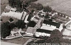 """Urte Mølle luftfoto: Luftfoto af Urte Mølle engang i 1930-erne. Bygningerne ligger på en lille """"ø"""" afgrænset af åløbet foran og af """"bagløbet"""" bag de bageste udhuse. Til venstre ses de daværende hønsehuse og den store tilhørende hønsegård. Privat foto."""